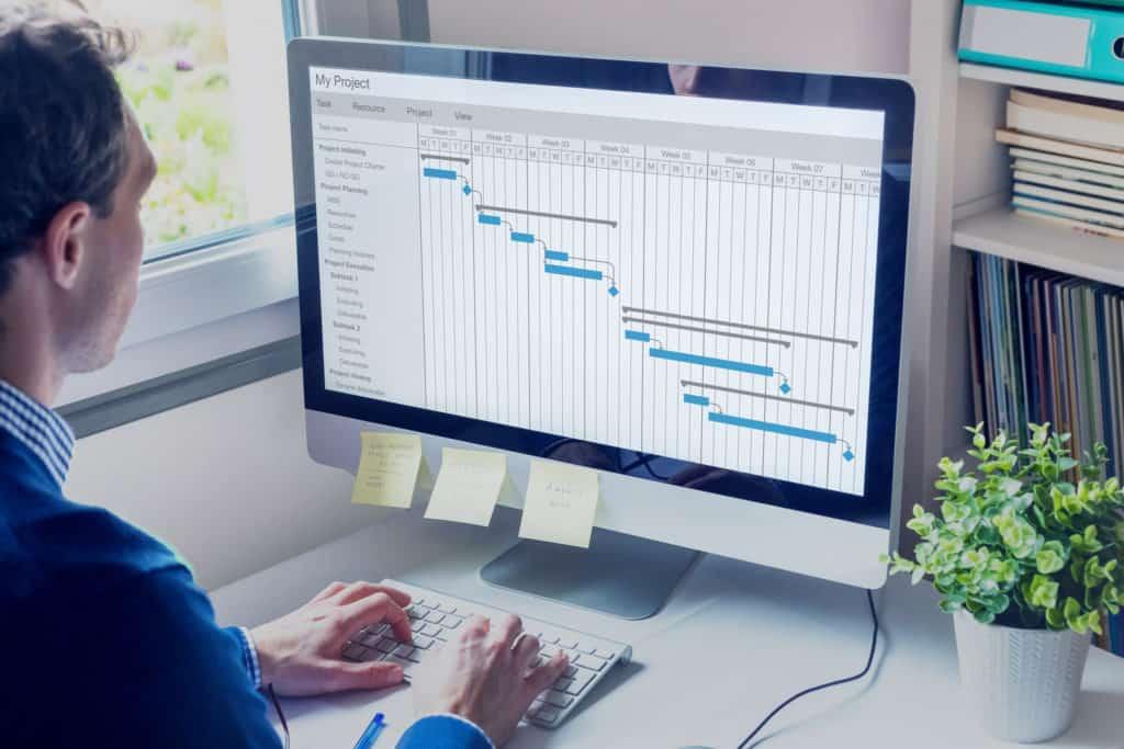 Mitarbeiter bearbeitet Gantt-Diagramm an PC-Arbeitsplatz zur Berechnung der Durchlaufzeit