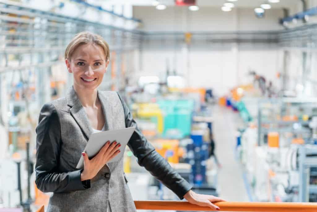Erfolgreiche Planerin steht vor ihrem Ergebnis der fertig geplanten Fabrik im Hintergrund