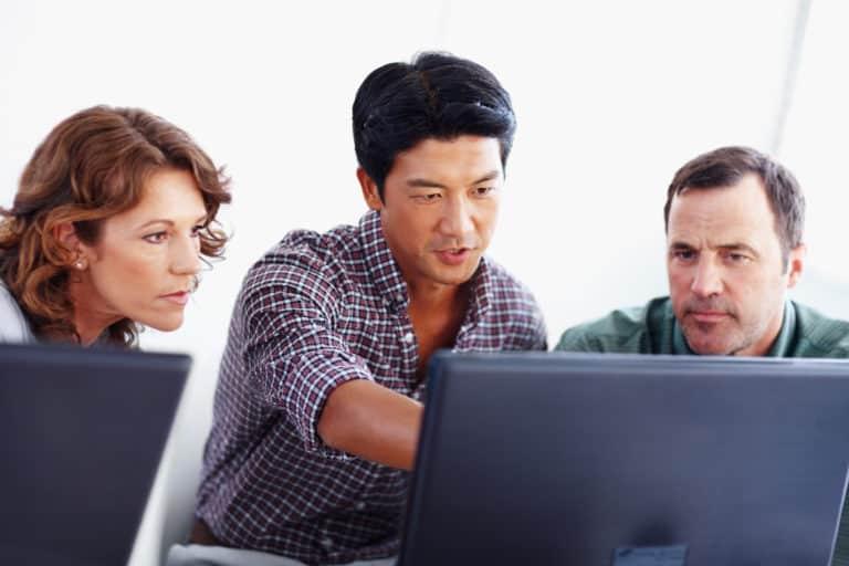 Kollege zeigt neue Planungssoftware für Fabrikplanung auf Notebook im Kollegenkreis um Sponsoren zu gewinnen
