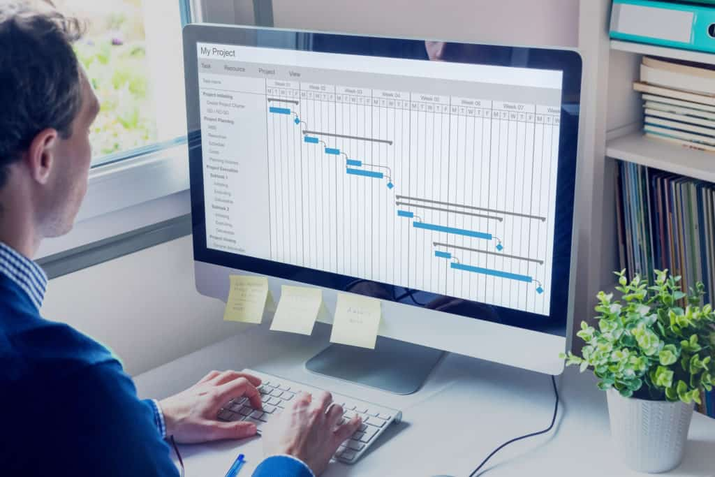 Employee edits Gantt chart at PC workstation to calculate lead time