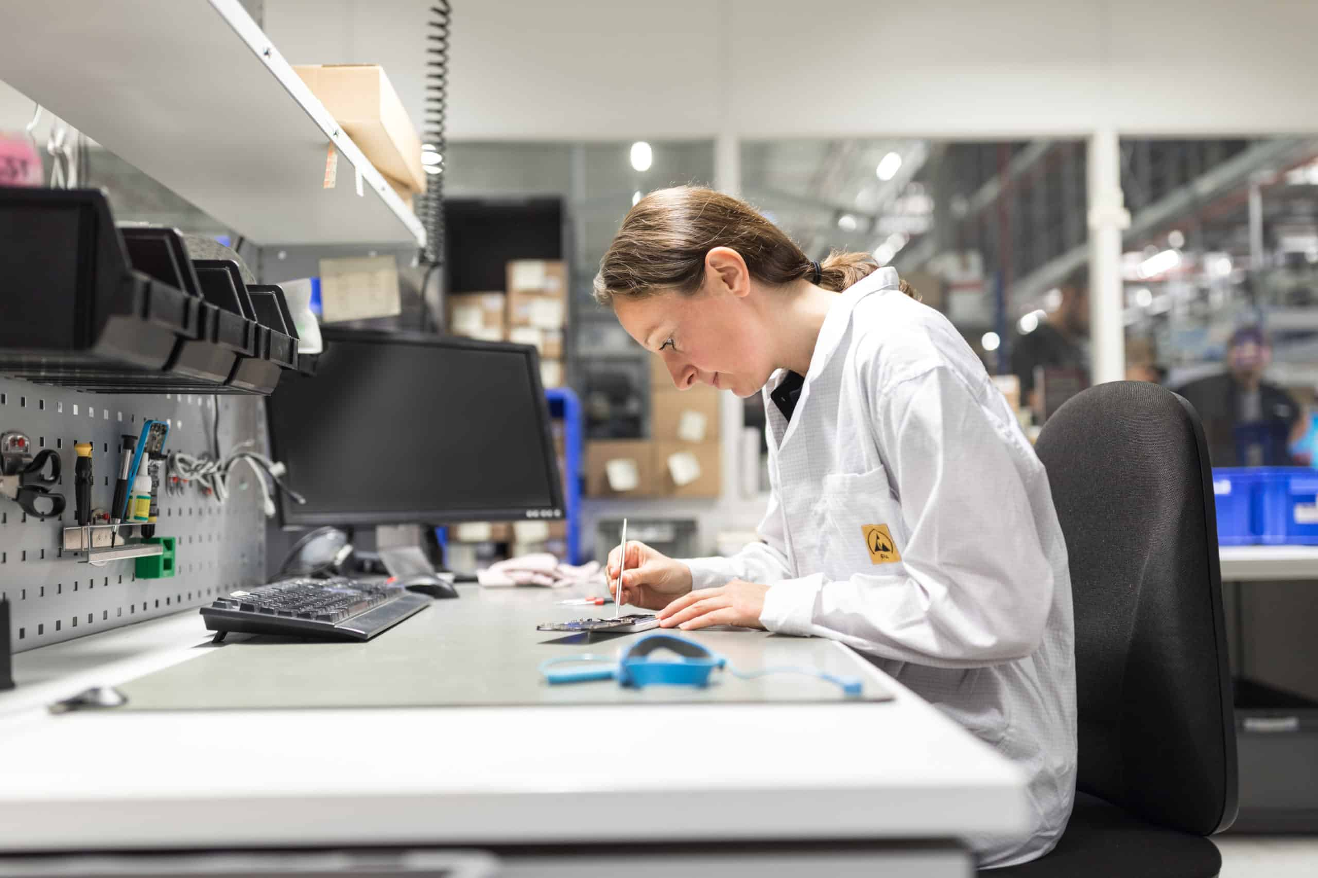 Employee at repair station for smartphones in a production facility