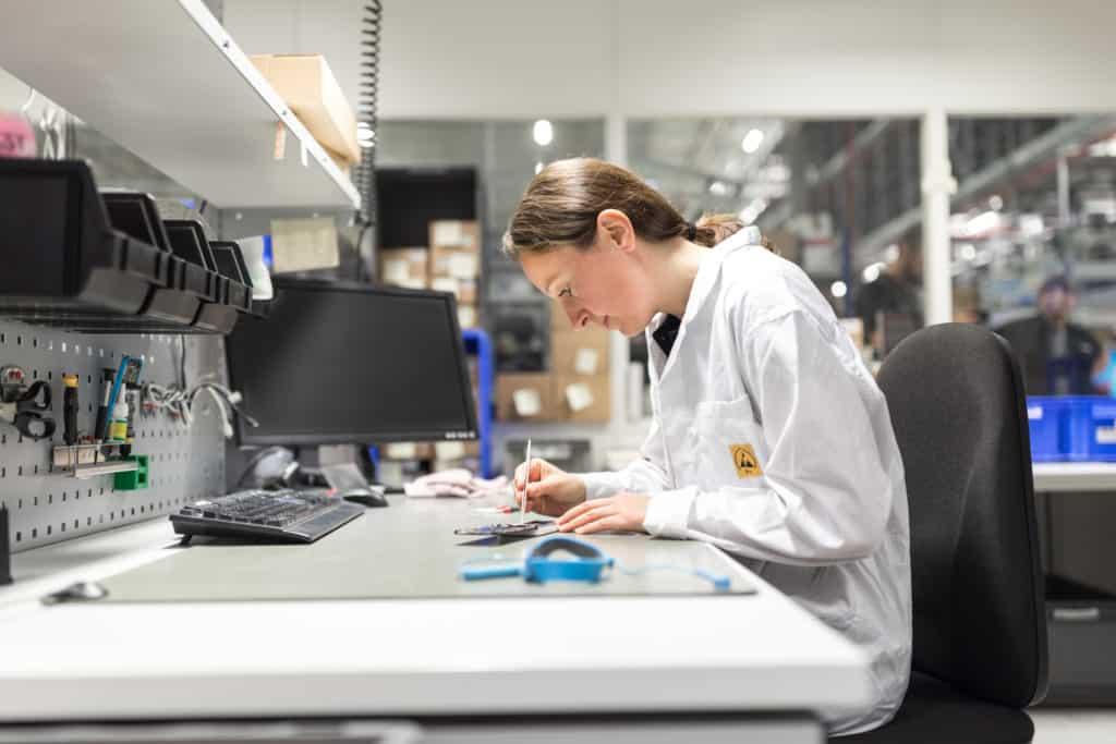 Mitarbeiterin an Reparaturstation für Smartphones in einer Produktion