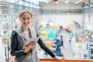 Successful planner stands in front of her result of the finished planned factory in the background